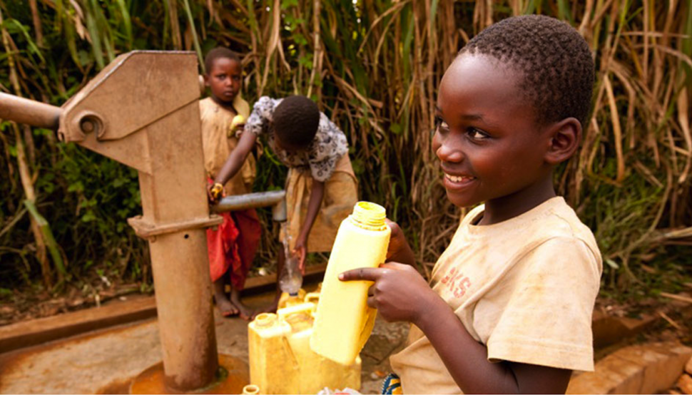 Young black children drinking water from a fresh water well - happy and smiling