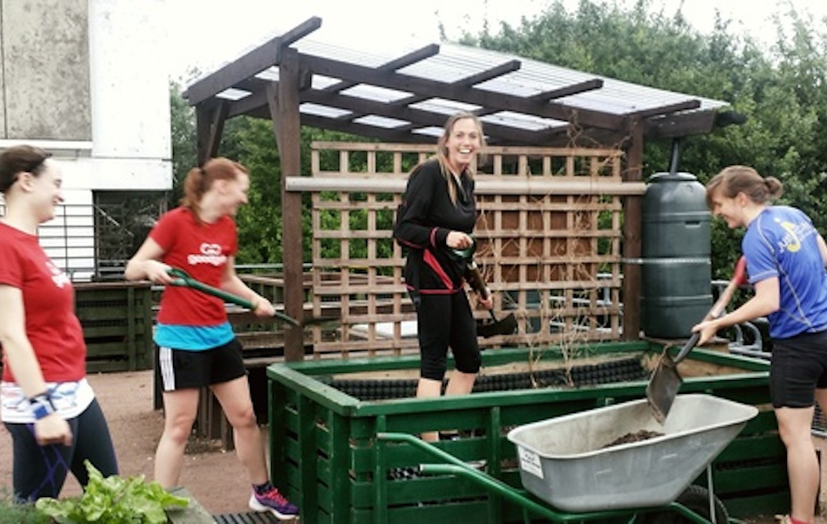 Group of GoodGym runners smiling as they work in a community garden