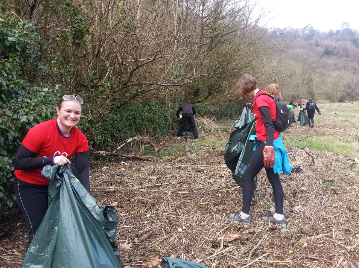 Group of smiling female GoodGym runners clearing up a field in Bristol