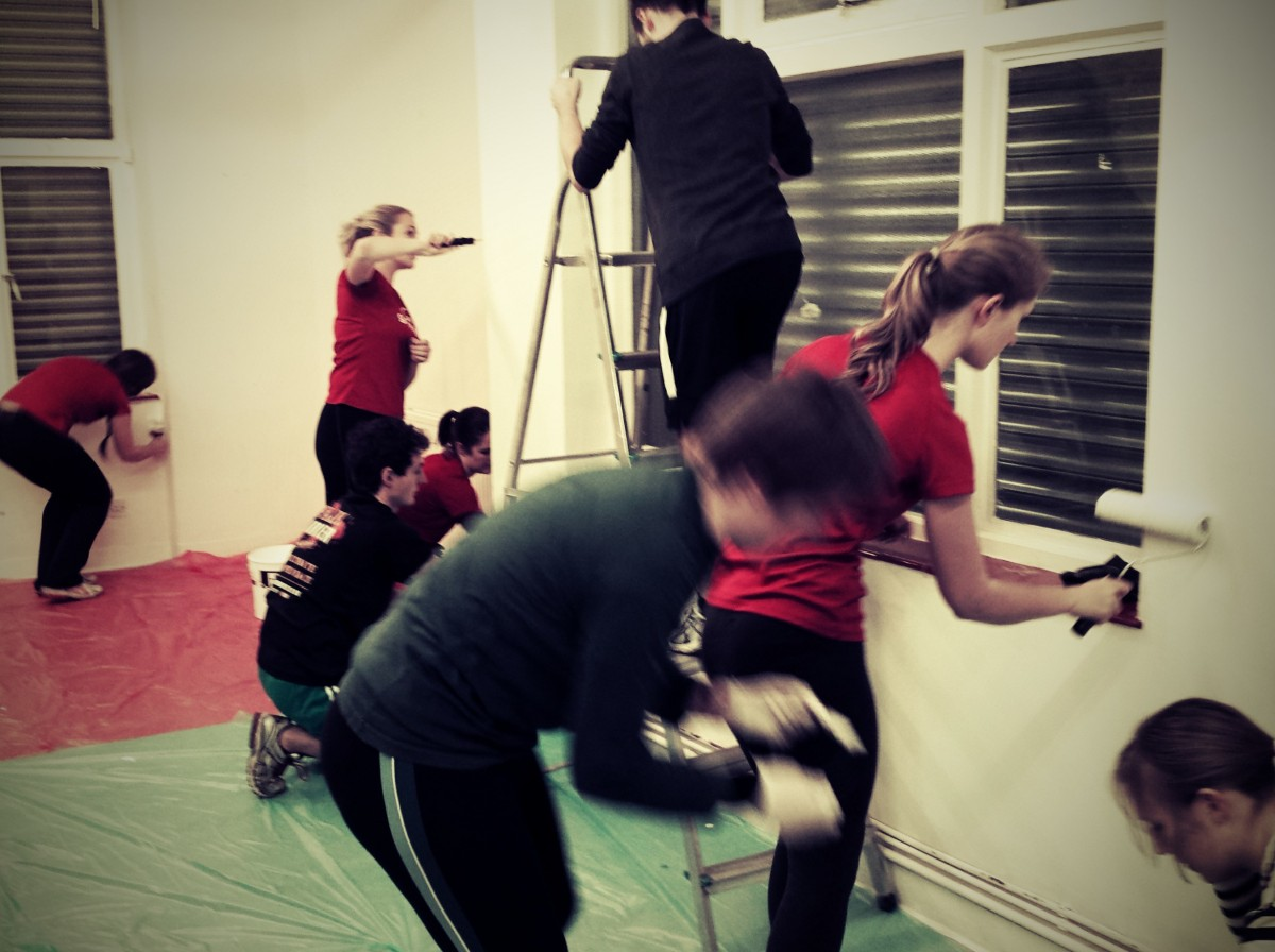 Group of GoodGym runners painting the inside of a community hall in London