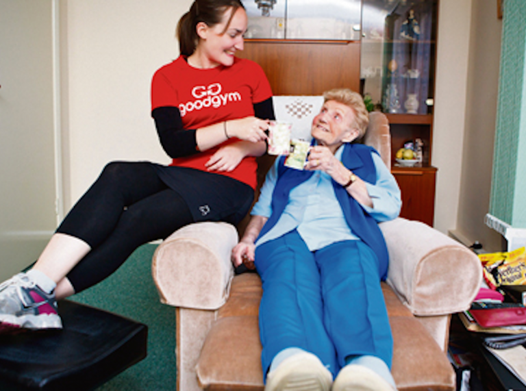 Female GoodGym runner having a cup of tea with an elderly lady in her home