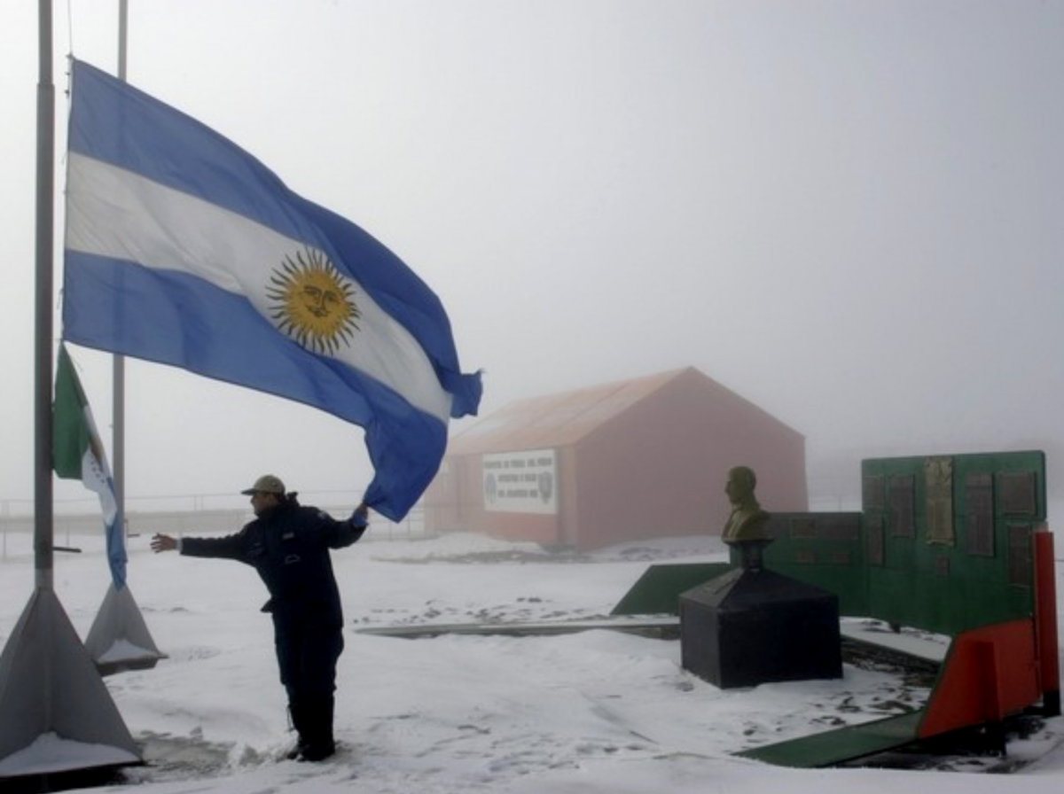 Man holding the edge of a large Argentinian flag flying at Marambio Base Antarctica during a snow storm (picture by Javier Gallo-Flickr)