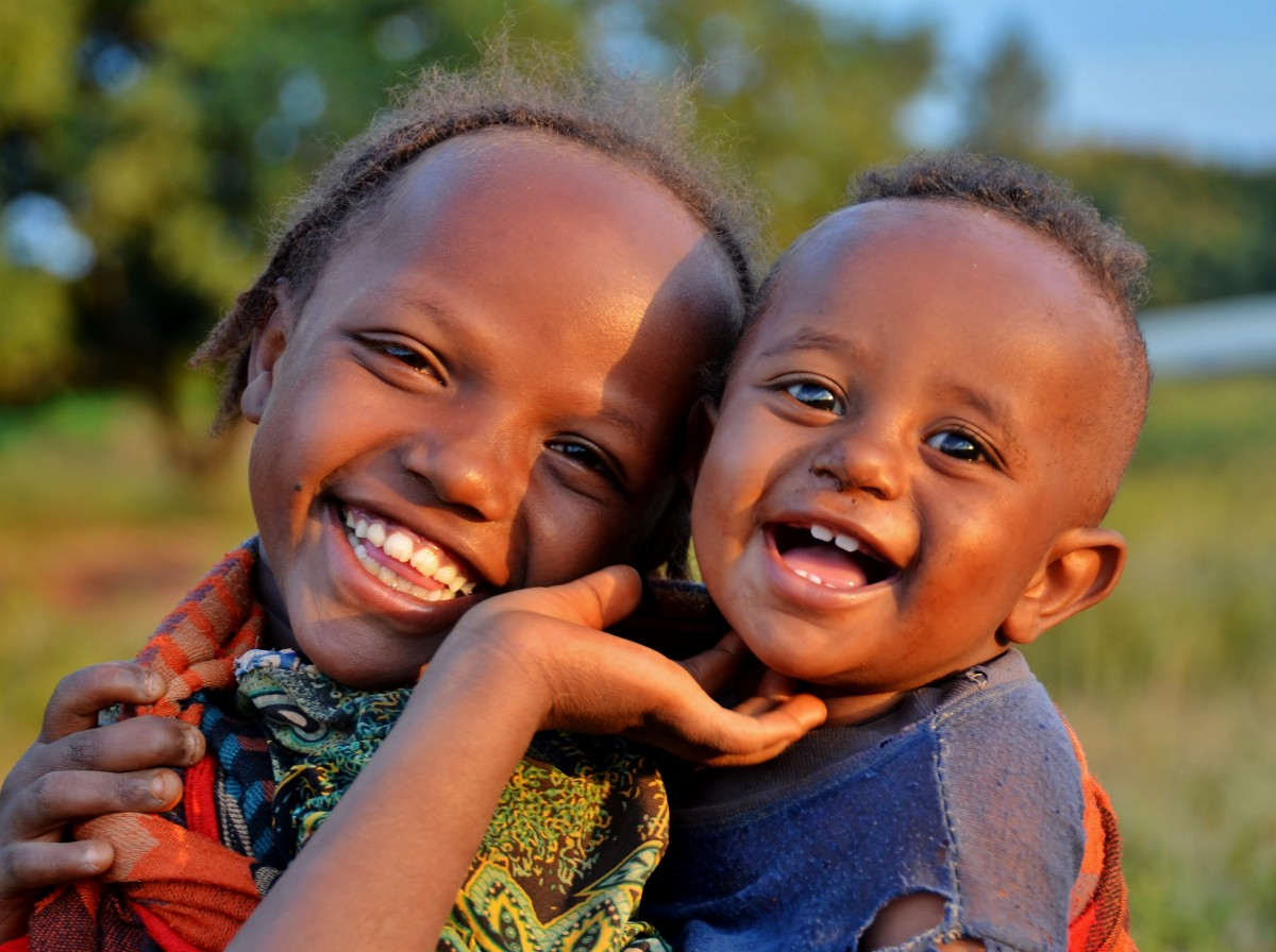 Two young smiling children from the Belo region of Ethiopia. The girl who is around 10 is holding a younger boy - Gymtopia.org