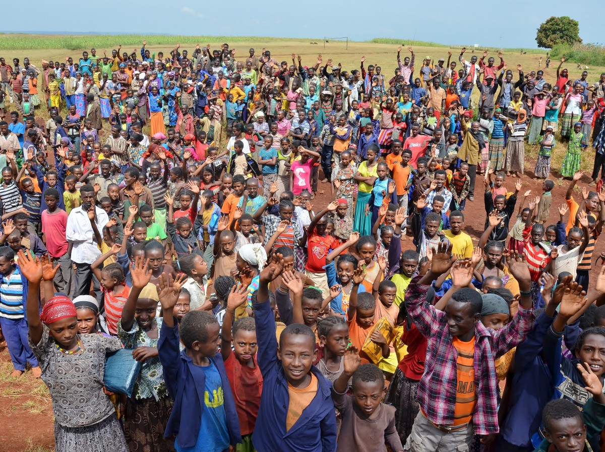 A large group of people living in the Belo region of Ethiopia are waving at the camera – Gymtopia.org