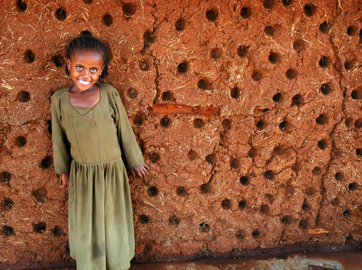 A young girl from the Belo region of Ethiopia is smiling. She is dressed in a long olive coloured dress and standing next to a mud wall which creates a lovely contrast – Gymtopia.org