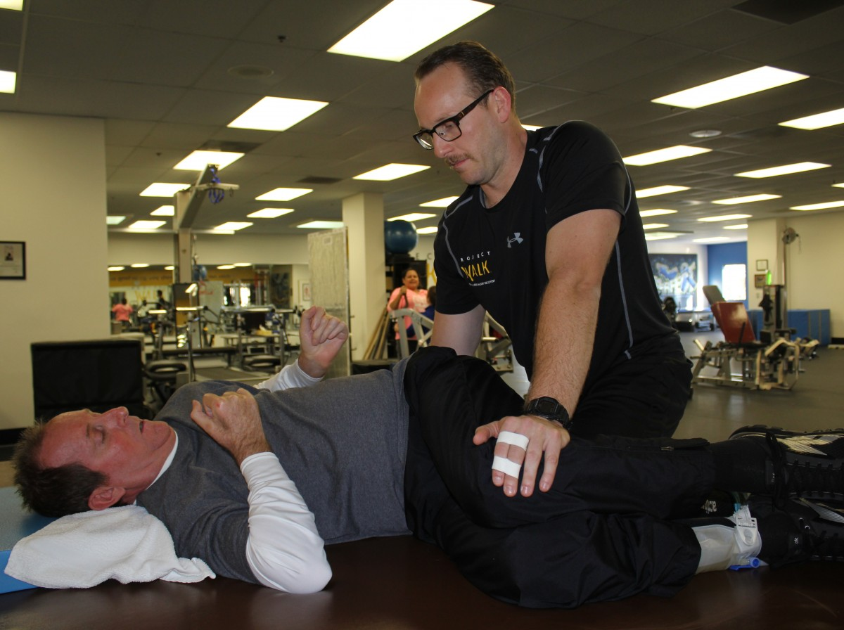 The male project Walk is on his back while the trainer helps to stretch the client's hips