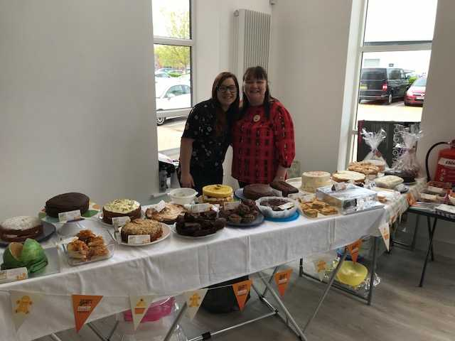 Legend Club Management staff Jayne and Jade raising money for UK cancer charities. They are standing behind a large display of cakes.