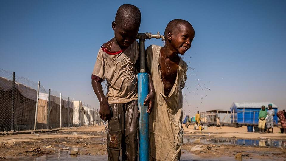 Two smiling young children collect water from the local community water well - The Les Mills/UNICEF project