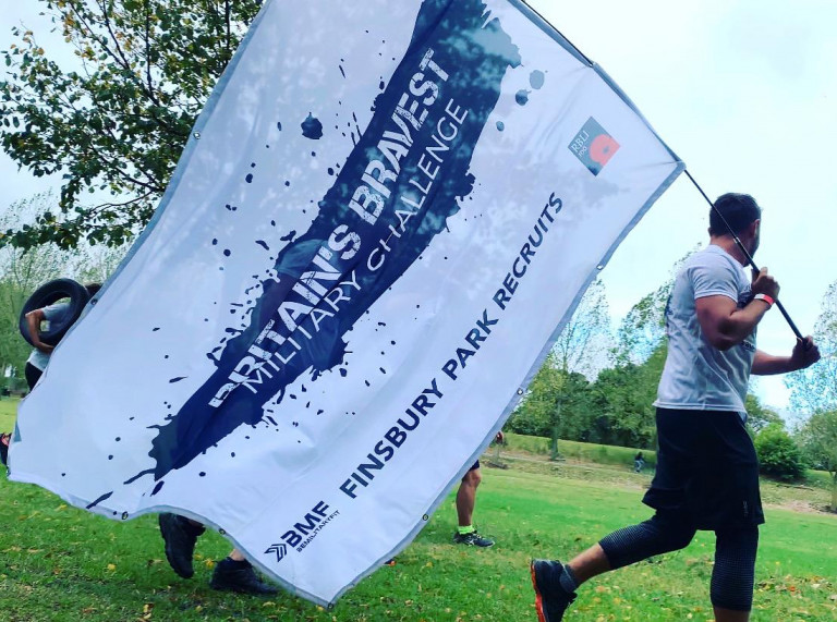 """Man running in Finsbury Park London with a BMF banner which says """"Britain's Bravest Military Challenge"""" which refers to supporting the Royal British Legion Industries (RBLI)"""